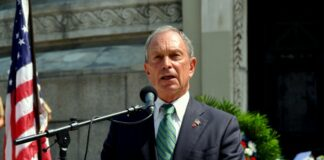 michael bloomberg speaking into a podium mic outside of a building, with a flag next to him