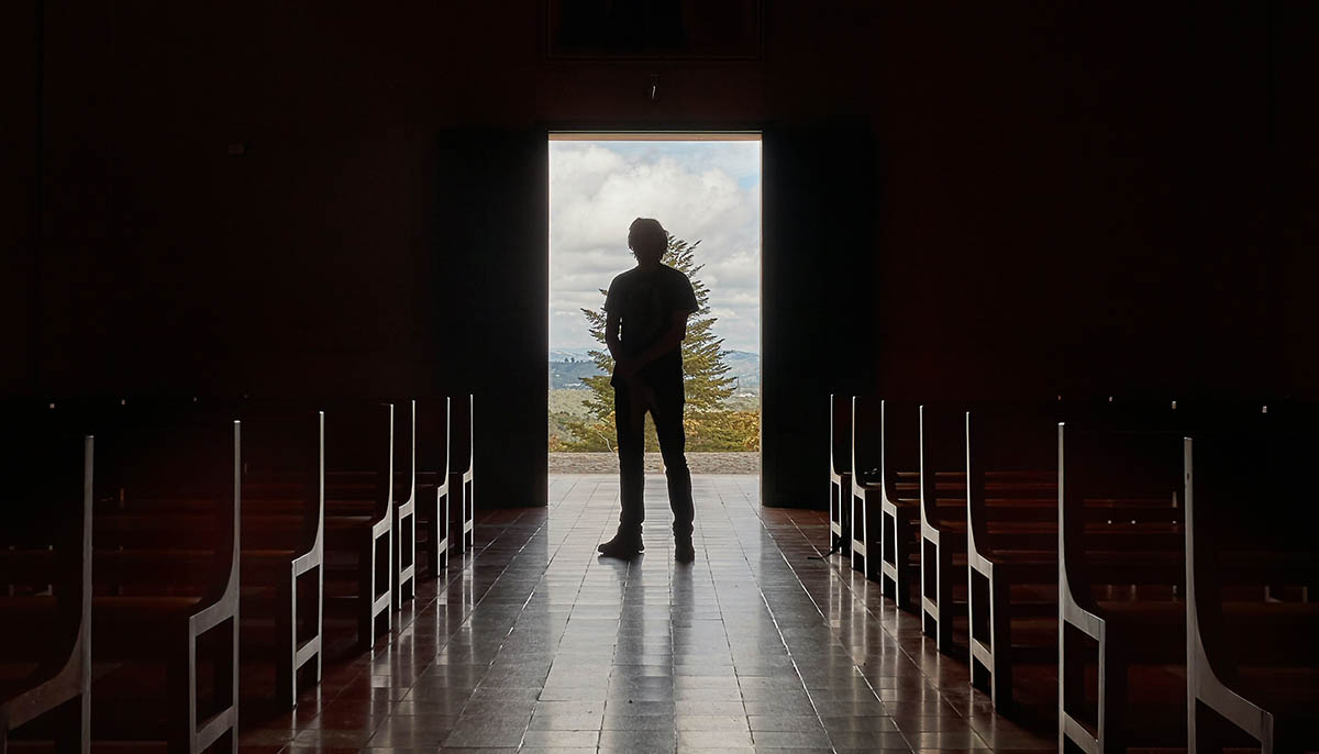 silhouette of a man inside of a dark church entrance