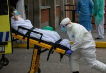 a man in a hazmat suit pushing a woman on a stretcher